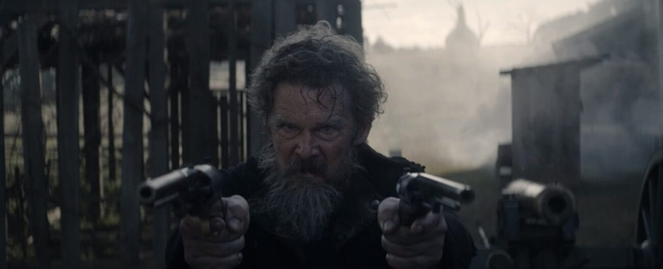 John Brown (Ethan Hawke) stares angrily at the camera with a gun in each hand pointed forward, behind him in the background is a dark building and a smoking cannon.
