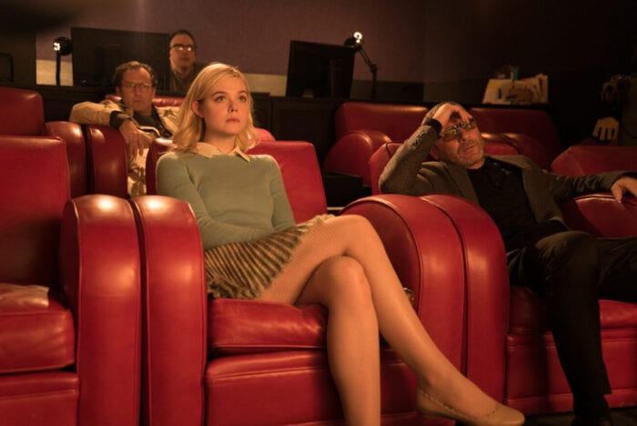 Ashleigh sits in a small theater watching a screening with the director and screenwriter.
