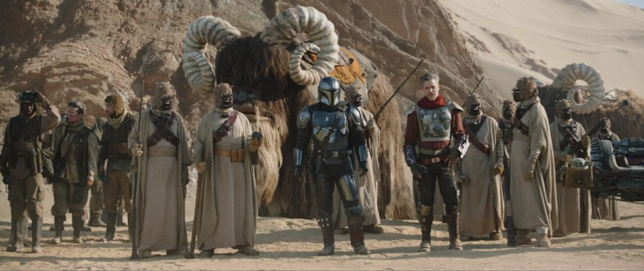 The Mandalorian, Cobb Vanth and Tusken Raiders stand in the desert, wit a Bantha in the background