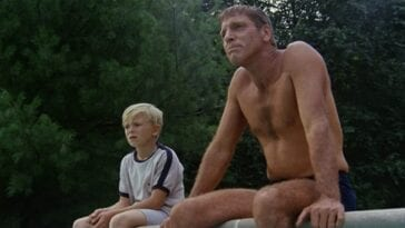 An image from The Swimmer 1968. Ned Merrill (Burt Lancaster) sits next to a young boy named Kevin Gilmartin Jr. on the edge of an empty swimming pool. Lancaster is shirtless and only wearing a small blue bathing suit. Both are staring into the distance.