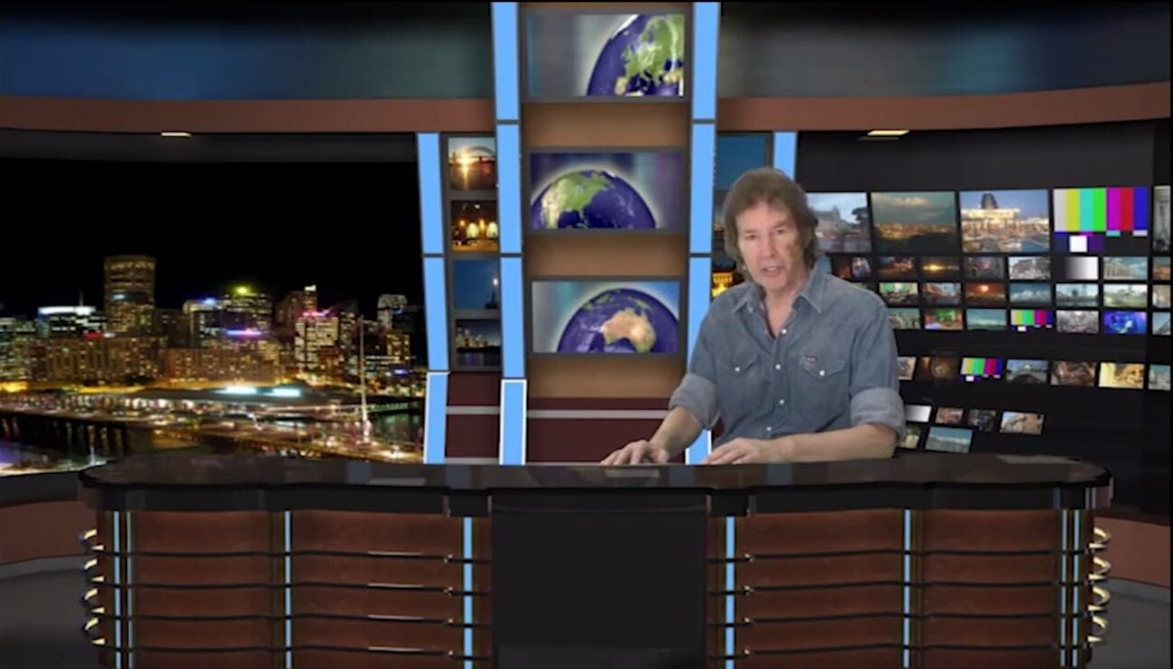 Neil Breen sits at a news desk to deliver his climactic speech at the end of Pass Thru. The background is an obvious green-screen.