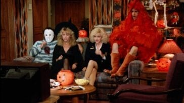 Larry wearing a hockey mask with a knife in his chest sits on a couch next to Jennifer in a witch's costume, Mary Anne in a flight attendant's uniform and Balki in a Chicken outfit watching tv