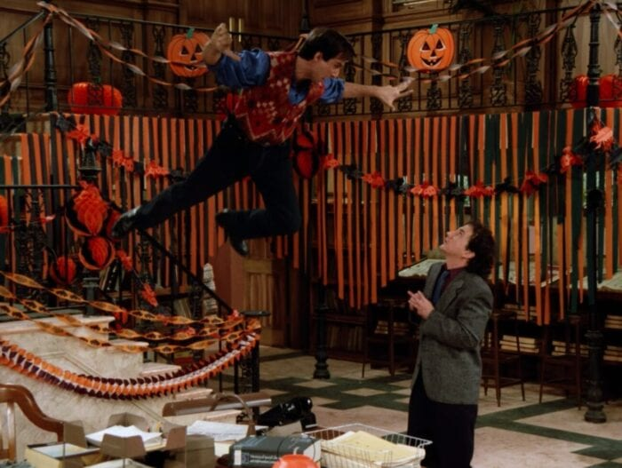Balki floats above Larry, his arms and legs flailing around a heavily halloween decorated office, Larry looks frightened underneath