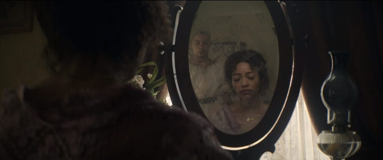 Pie (Natasha Marc) sits in shadows with her back to the camera looking into a mirror, in the oval mirror Pie's reflection is looking down while Onion stands behind her