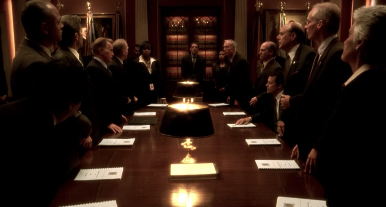 Men and women in dark suits surround a long table