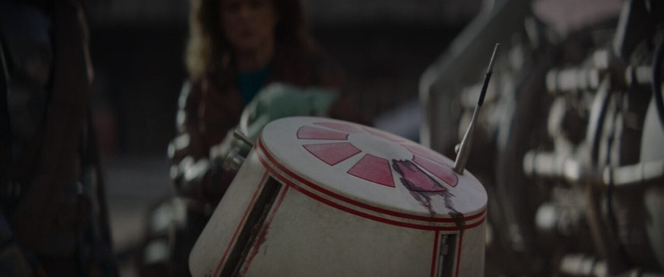 R5-D4 rolls towards The Mandalorian, Peli Motto and The Child, showing damage on his dome