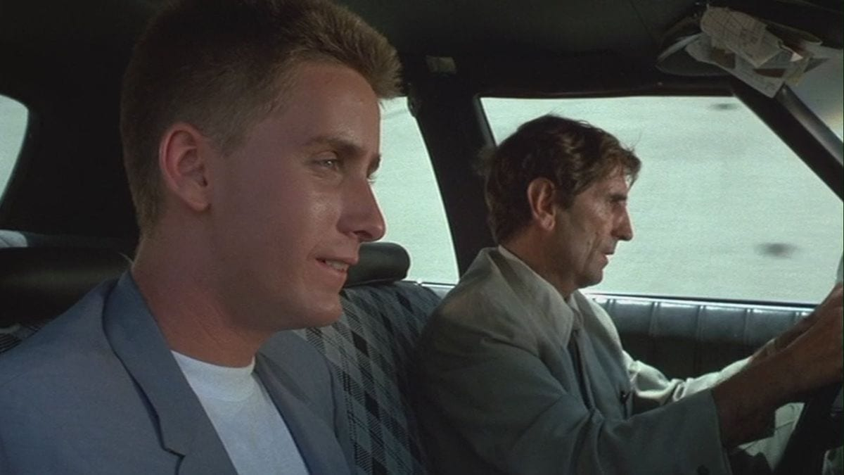 Emilio Estevez and Harry Dean Stanton drive around a city in Repo Man