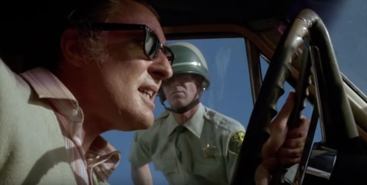 A dying driver of a mysterious car is confronted by a highway patrolman in Repo Man