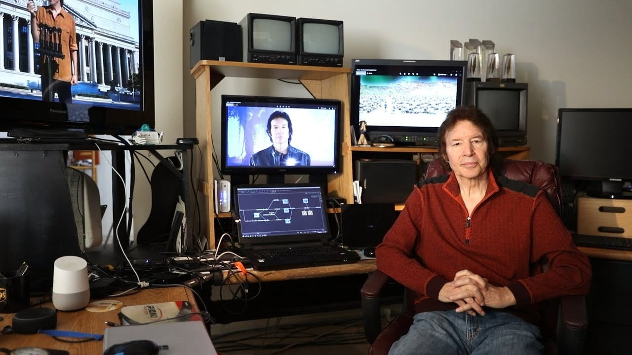 Neil Breen sits in his studio. Screens are on behind him with stills from his films.