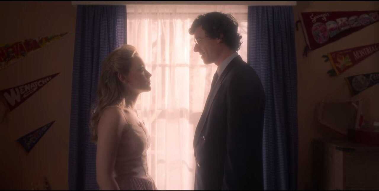 Dani and Edmund prepare one another for their engagement party, standing before a window looking at each other