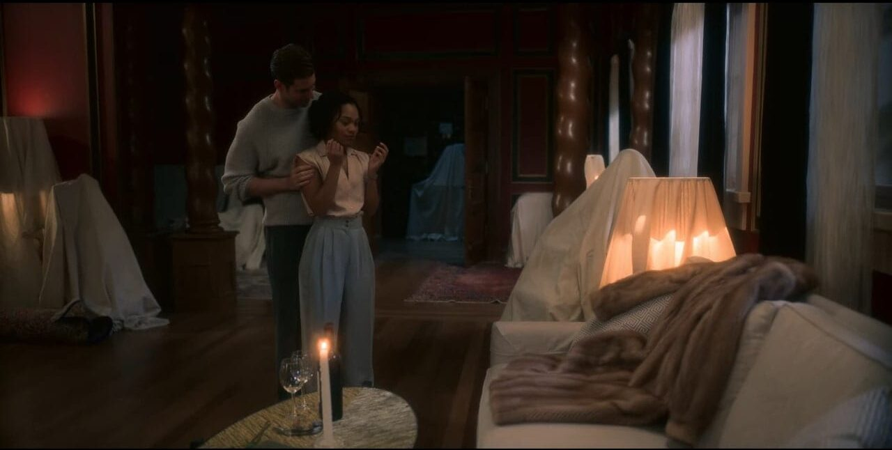 Peter holds Rebecca's arms as he presents her with a fur coat that lies on a couch