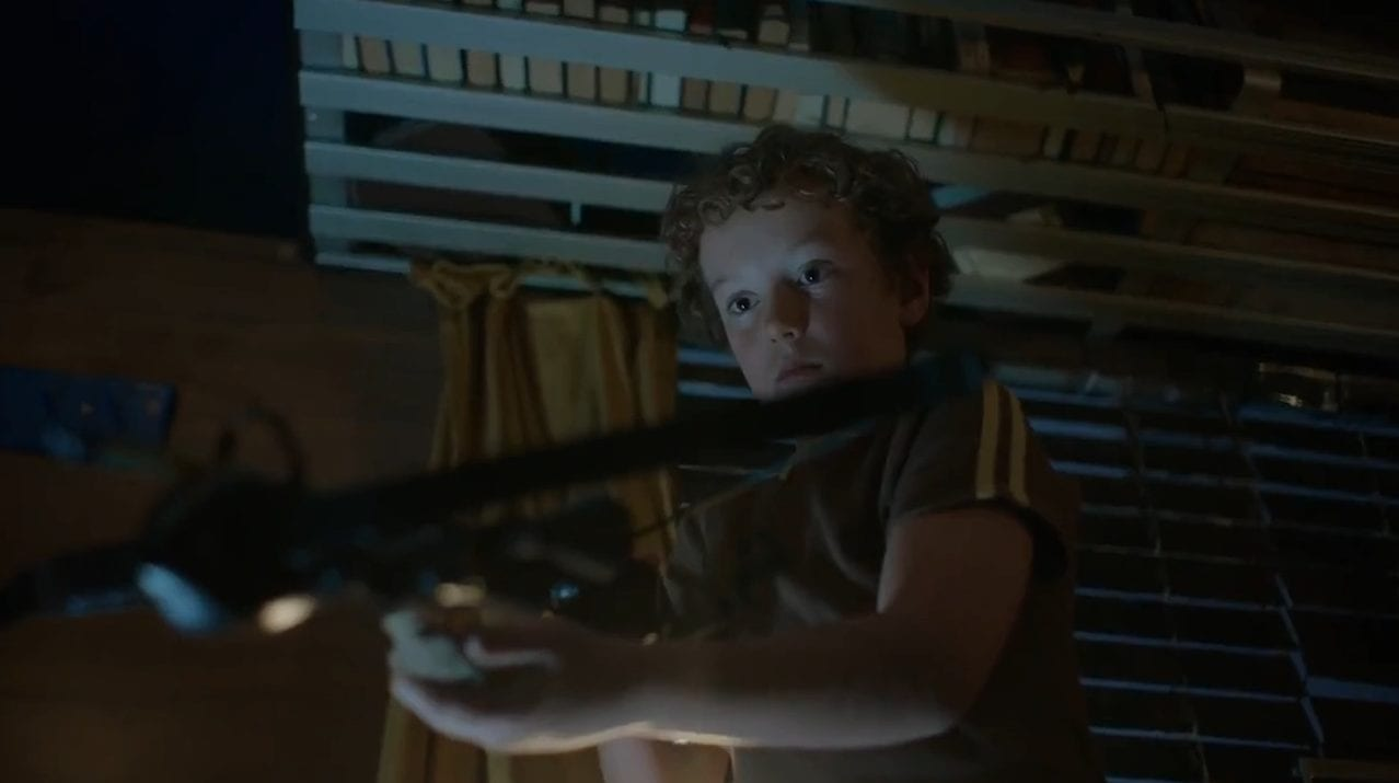 Charlie (Jack Ruwald) plays with a crossbow.