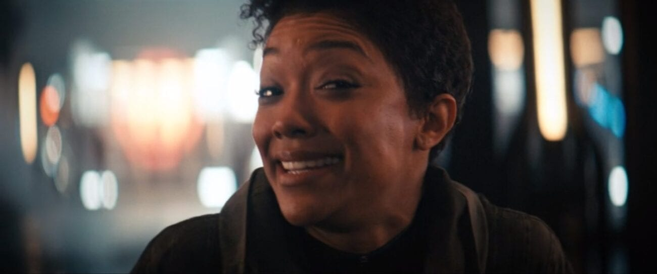 Michael Burnham (Sonequa Martin-Green) in the center of the shot looking toward the camera making a goofy face, the background is a series of blurry lights