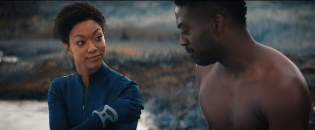 Burnham (Martin-Green) wearing her blue uniform, looking at a shirtless Book (David Ajala) while holding her hand to the wound at her shoulder in front of a rocky backdrop