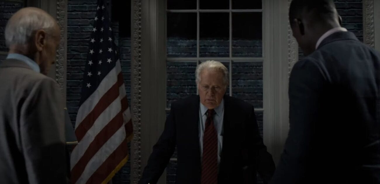 President Bartlet behind his desk with two officials looking on
