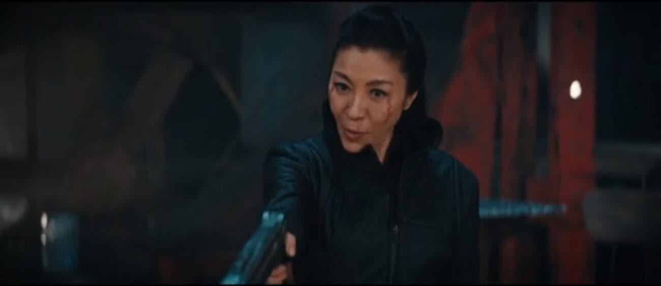 Georgiou (Michelle Yeoh) staring forward holding a phaser aimed in front of her and toward the ground with a a red and black blurred background