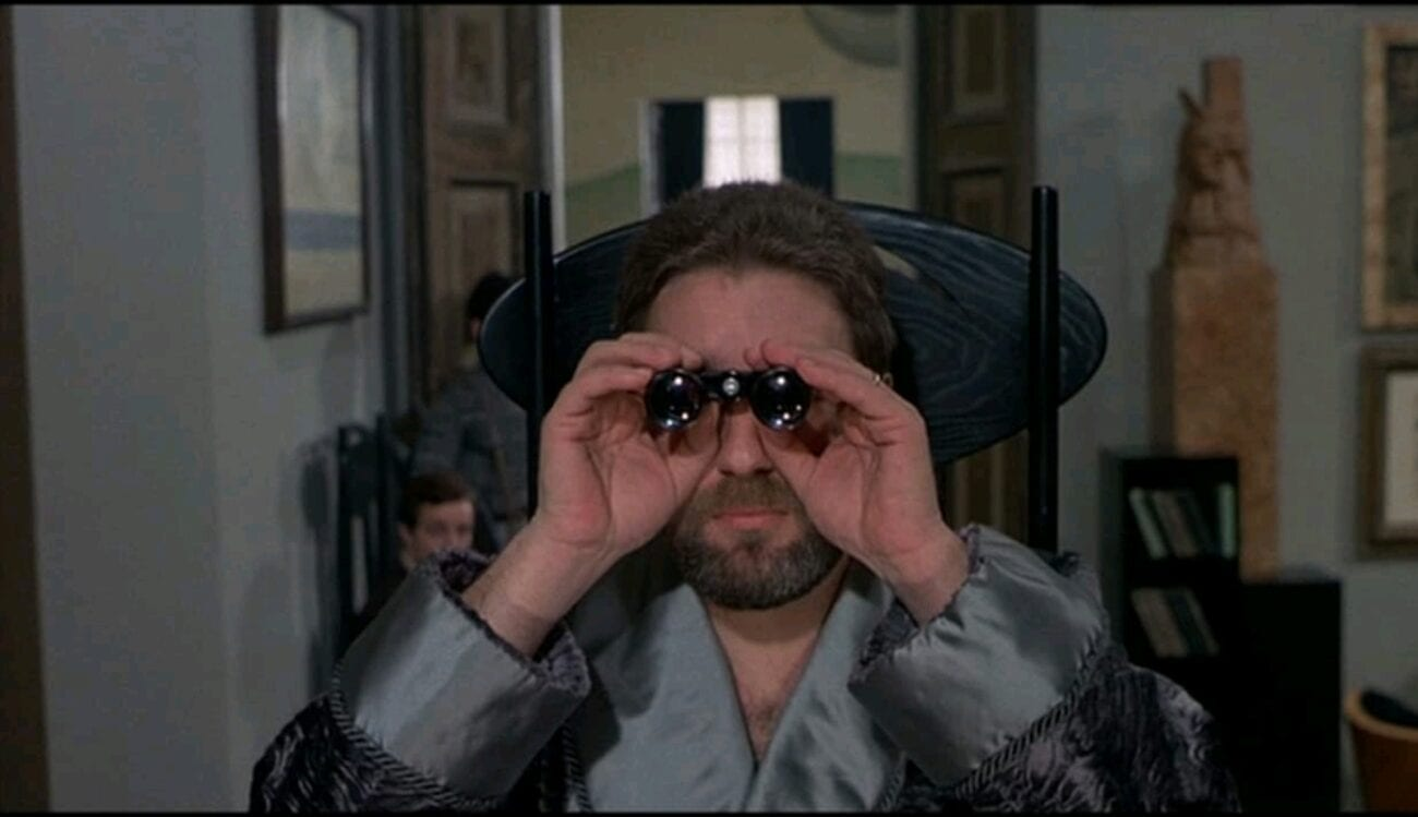 The Duke (Paolo Bonacelli) stares from a window with binoculars into the camera