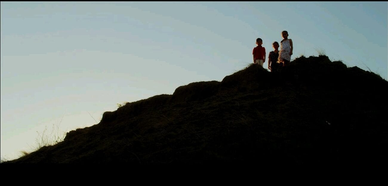 A low-angle shot of Eliza (Angeli Bayani) and her children JR (AJ Baliat) and Sarah (Aneeza Hernandez) looking down from a cliff