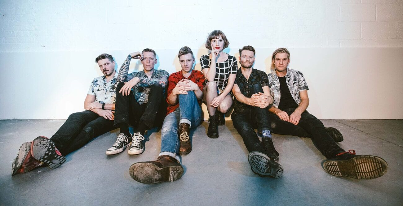 The six member of the band Skinny Lister sitting on the floor looking into the camera