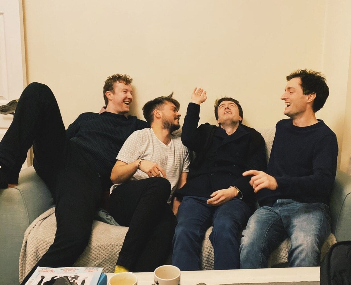 The four male members of the band Slender Pins laughing on a sofa