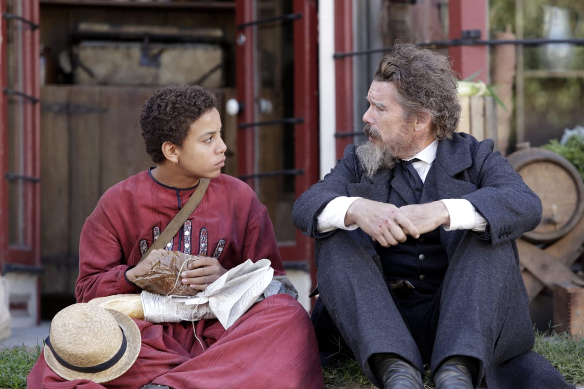 Onion (Joshua Caleb Johnson) in a red dress with a hat and parcel in his lap and John Brown (Ethan Hawke) with his arms crossed in front of his knees, sitting on a stoop looking at each other