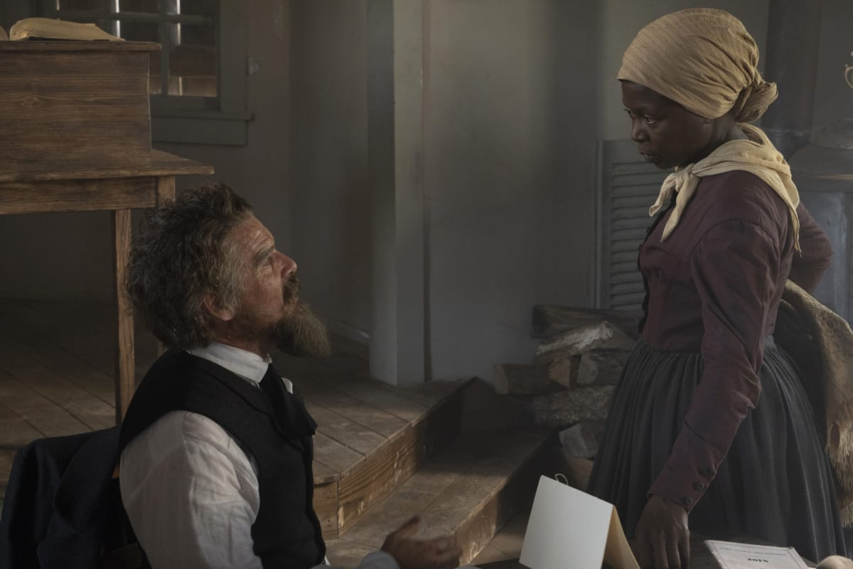John Brown (Ethan Hawke) sitting at a desk on the left looking up at Harriet Tubman (Zainab Jah) as she looks down at him