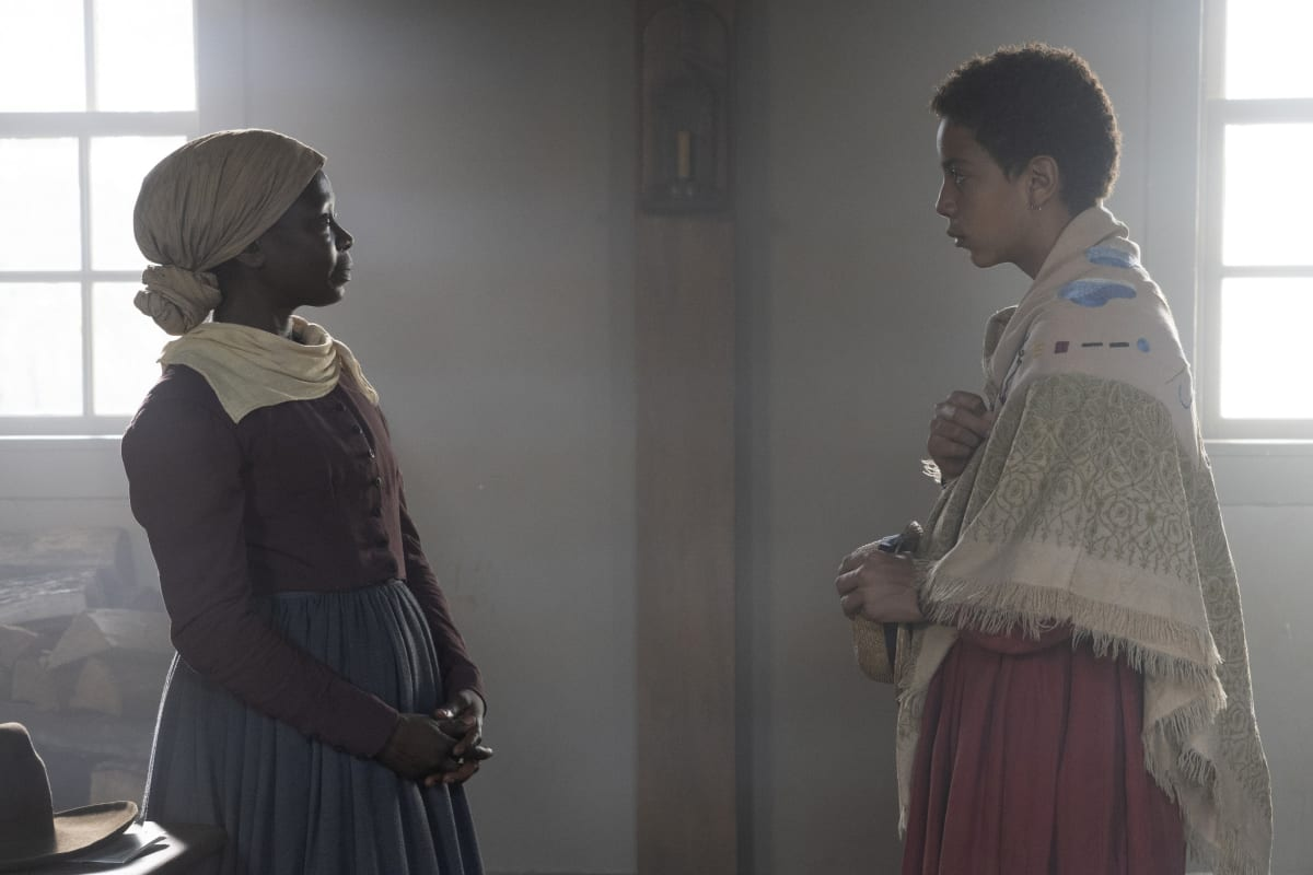 Harriet Tubman (Zainab Jah) looking at Onion who is wearing a shawl and red dress in a white room with two windows in the background