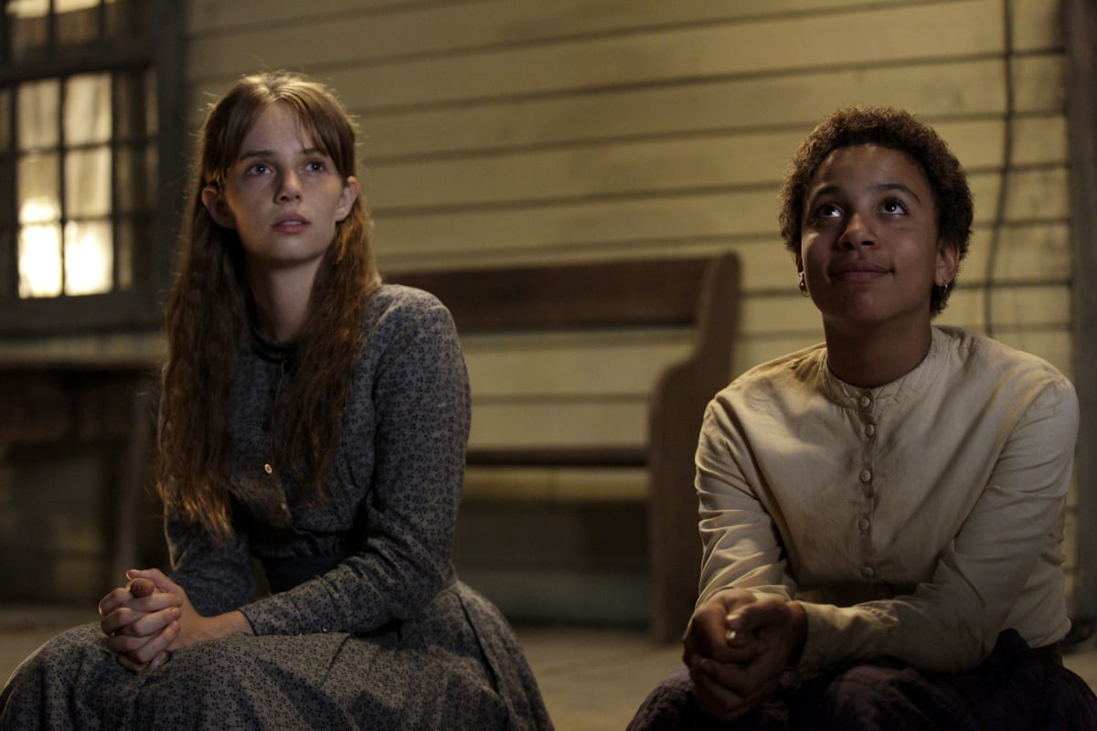 Annie Brown (Maya Hawke) and Onion (Joshua Caleb Johnson) sitting on the porch of a white house with a brown bench behind them, looking up at the sky
