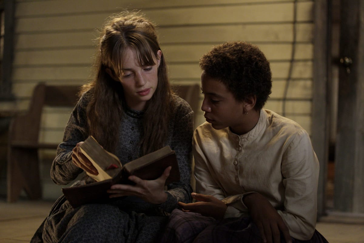 Annie (Maya Hawke) and Onion (Joshua Caleb Johnson) sit on the porch of a white house as he reads over her shoulder
