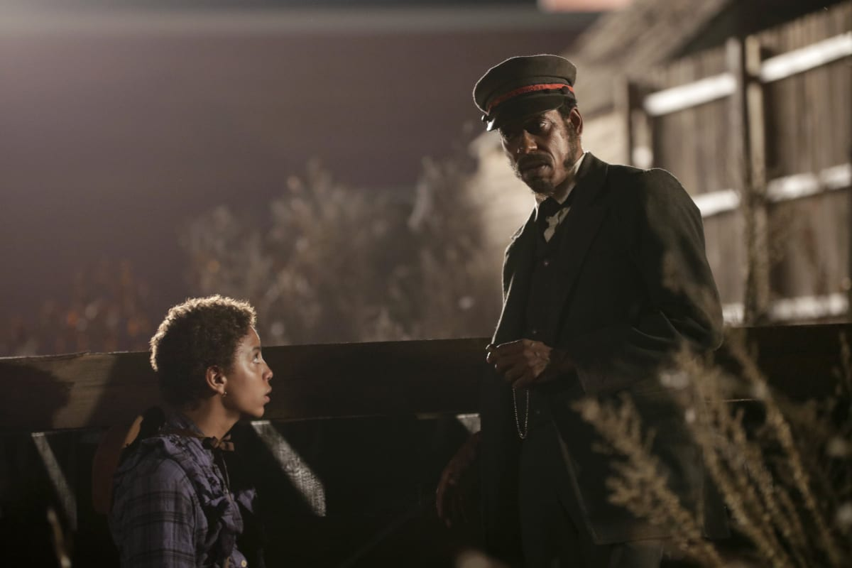 Onion sits low on the left as the Rail Man (Orlando Jones) listens with his hands at his hips, there is a train shelter in the back and shadows and smoke all around the two figures in the center