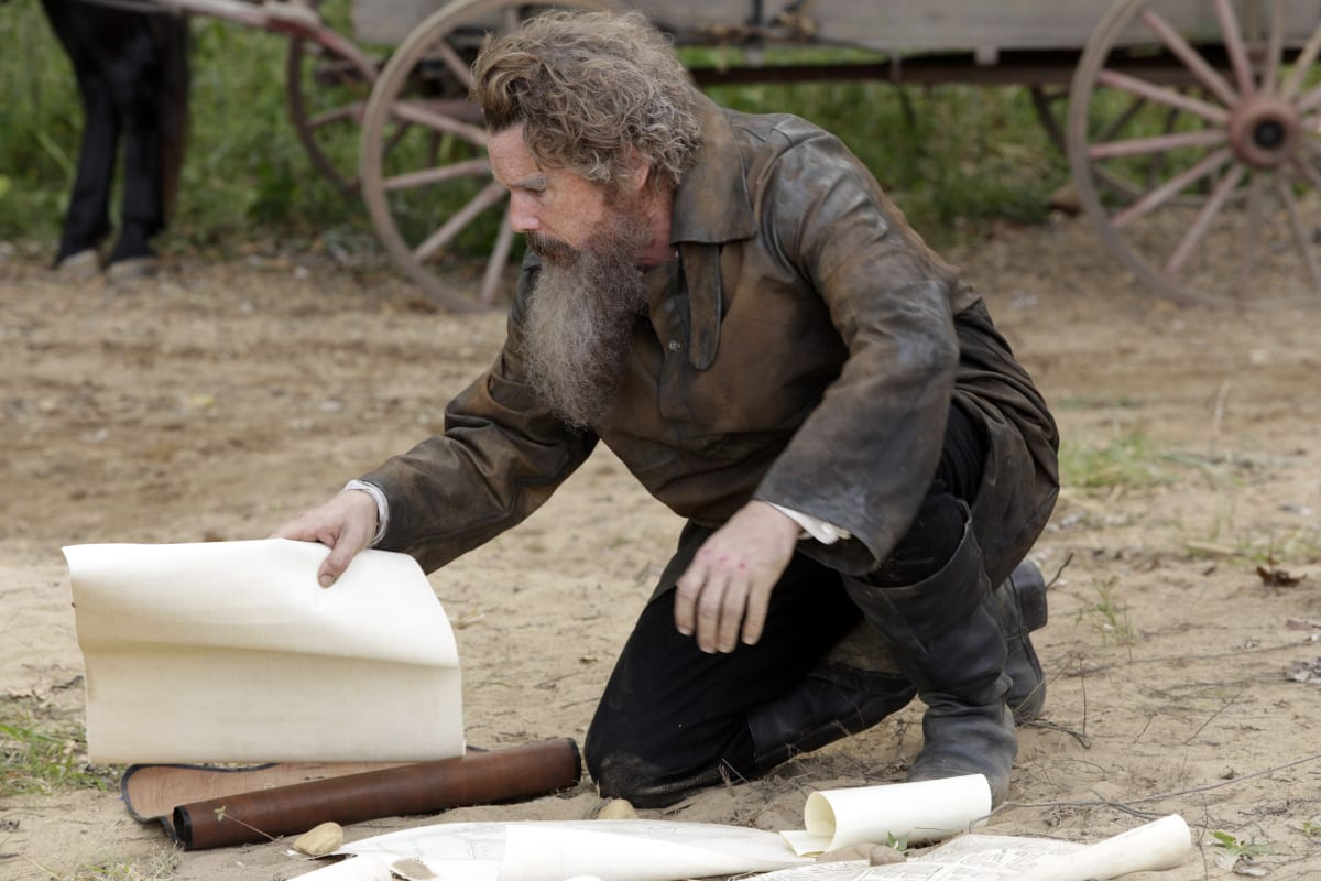 John Brown (Ethan Hawke) kneeling on the ground with a large white paper in his hand, other papers are scattered on the dirt in front of him, a wooden wagon in the background