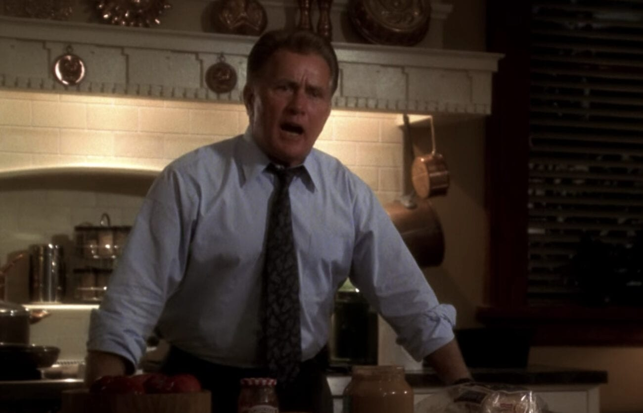 Jed Bartlet stands behind a counter in a shirt and tie, declaiming about something