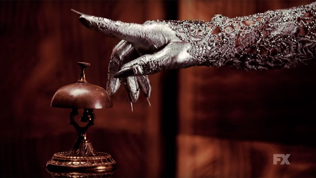 A silver hand with long nails reaches for a bell