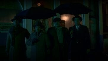 A line of men in coats and hats standing under umbrellas