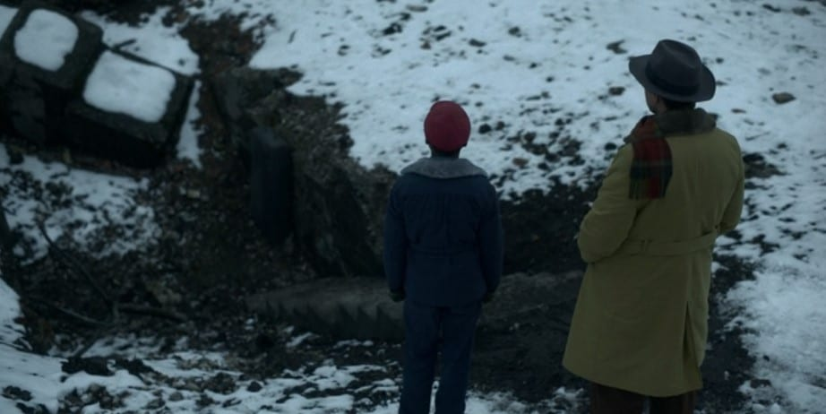 Antoon Domini escorts Satchel Cannon to a set of stone steps leading down into a pit in a snowy field.