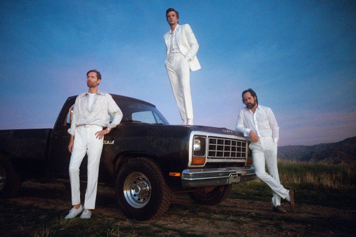 The three active members of the killers are dressed in white and leaning against a car