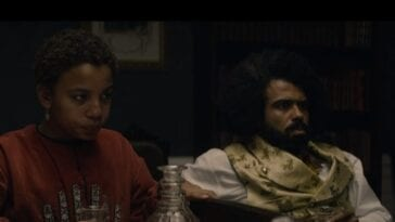 Onion (Joshua Caleb Johnson) and Daveed Diggs looking forlorn while holding empty glasses, sitting on a couch in a dark room