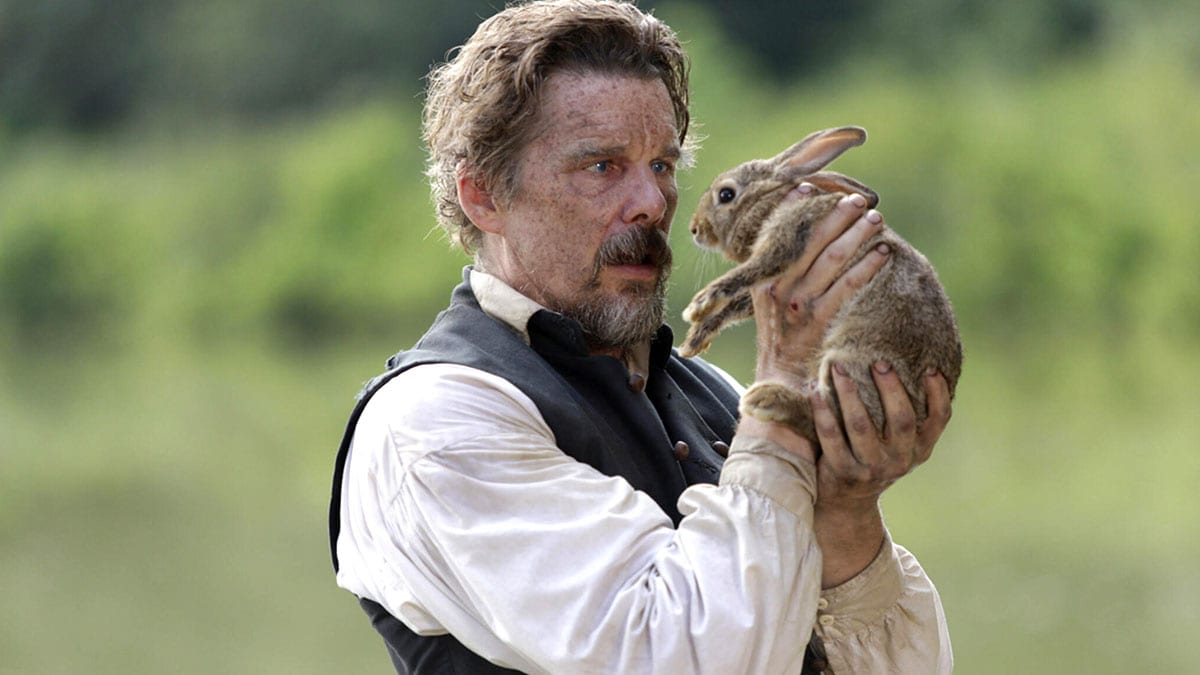John Brown (Ethan Hawke) standing in clearing of a wooded area holding a rabbit in his hands close to his muddy face.