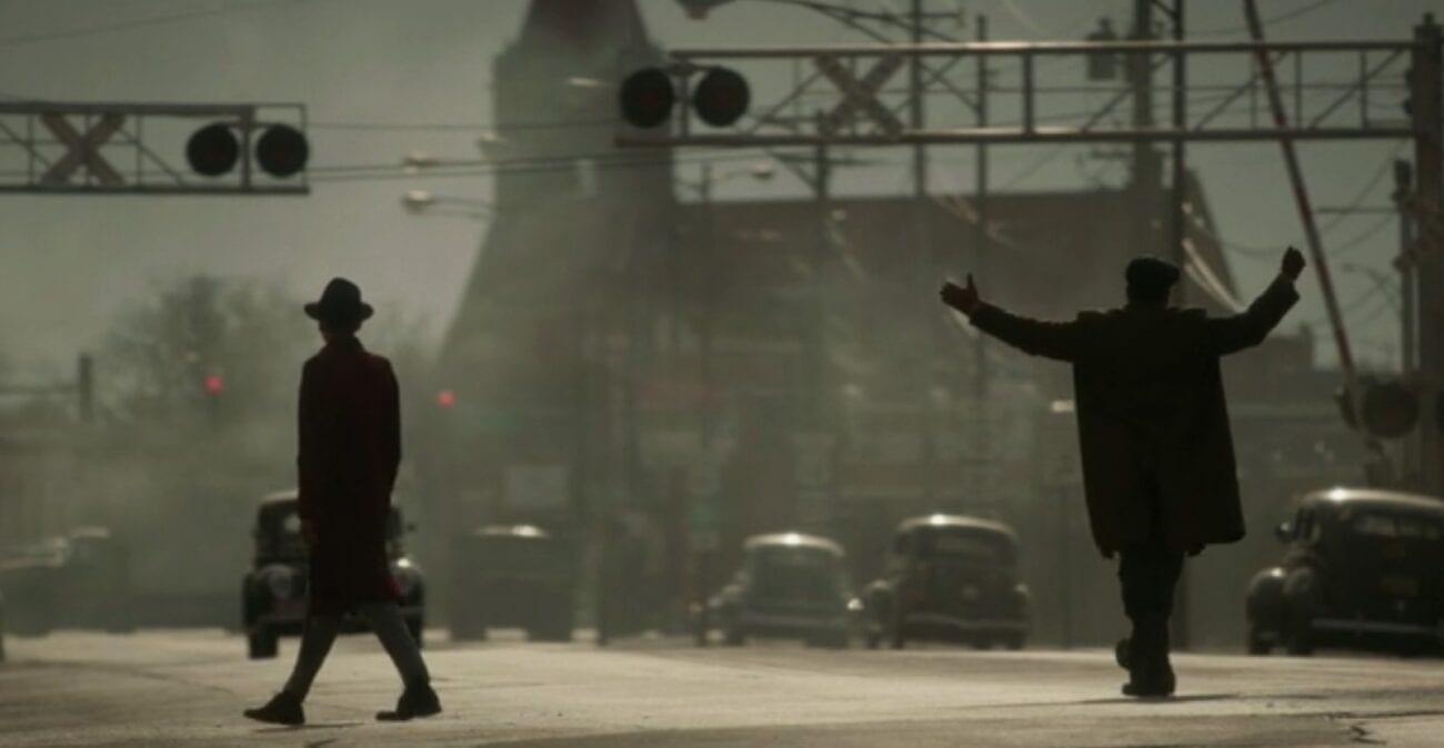 Gaetano dances across the street while his henchman Calamita stays a few feet ahead