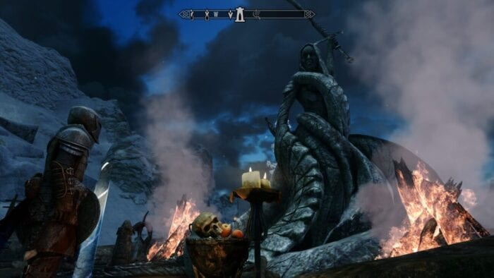 A statue of a serpent-like woman brandishing a sword is observed by a warrior in Skyrim.