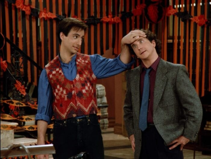 Balki in a multi-colored vest places his left hand on his cousin Larry who has his eyes crossed like he's under his control