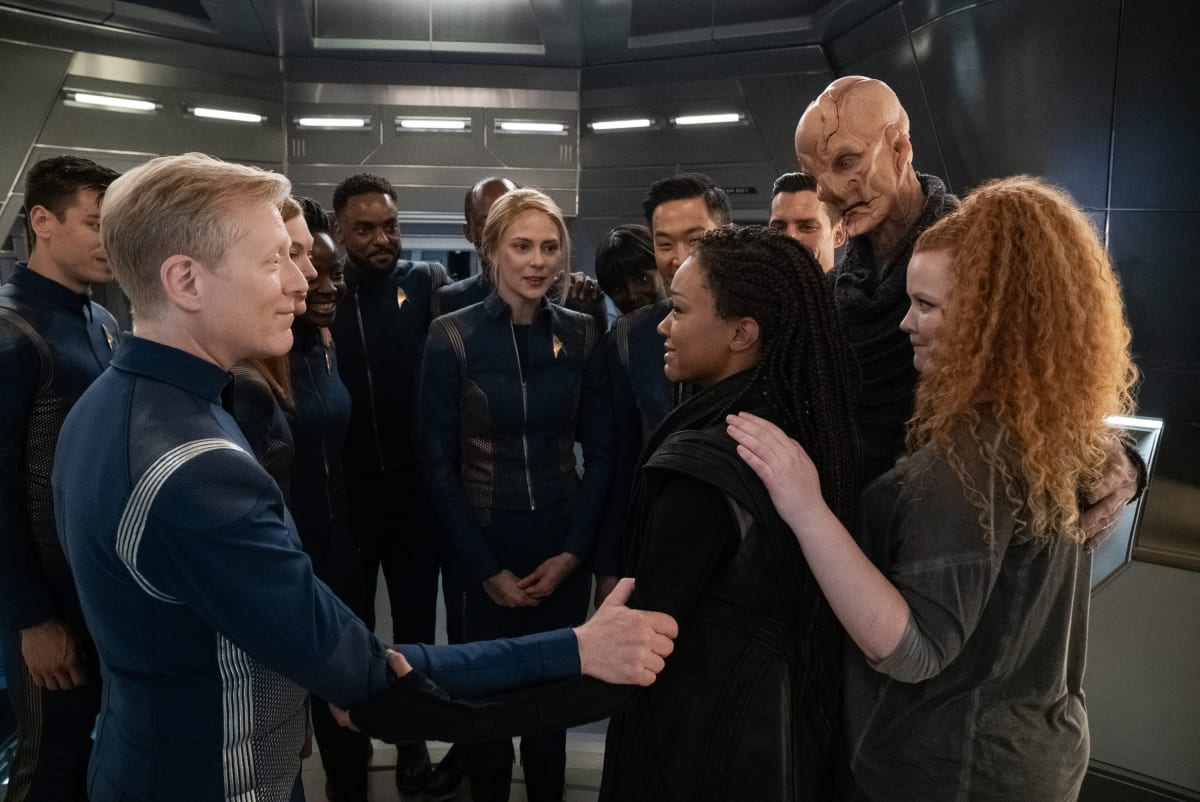 Stamets (Anthony Rapp) stands to the left with his arm on Burnham (Sonequa Martin-Green)'s arm, Tilly (Mary Wiseman) has her arm on Burnham's back as she stands to the right, Saru and the rest of the crew stand in the background