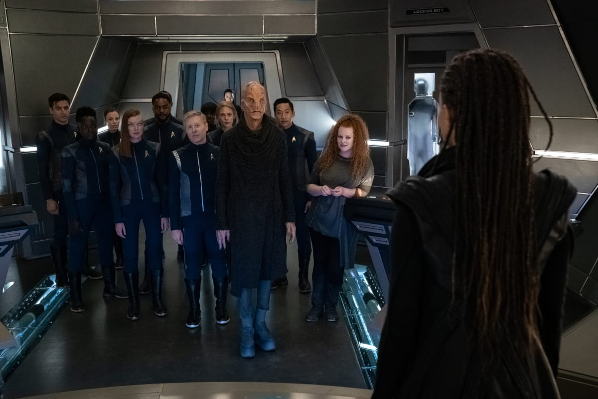 The Disovery Crew with Saru (Doug Jones) at center look toward the camera standing to the right as Burnham (Sonequa Martin-Green) beams aboard with her back to the camerain the transporter