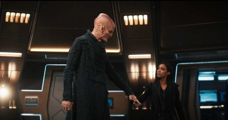 Saru stands on the Discovery bridge and looks at Burnham as she offers him the Captain's chair