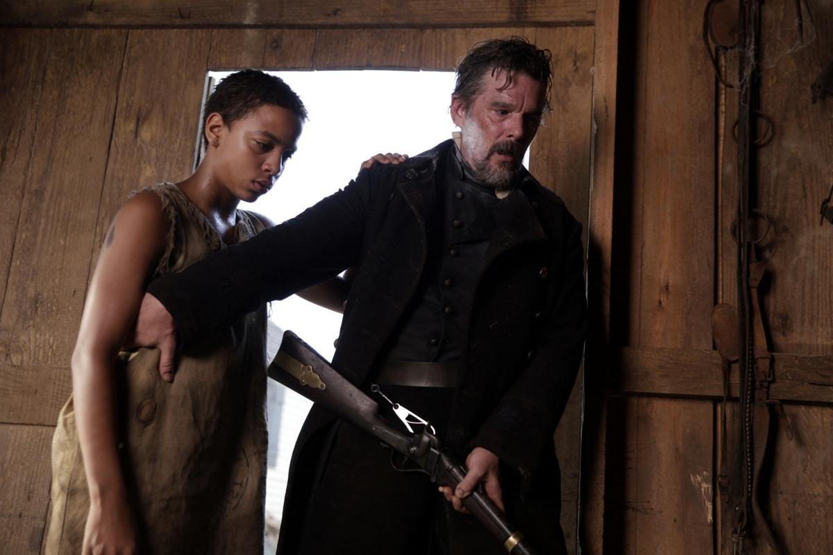 John Brown (Ethan Hawke) standing in a doorway of a wooden wall with light behind his back holding a shotgun at his hip with a hand on the shoulder of Henry as both look down at the ground with concern