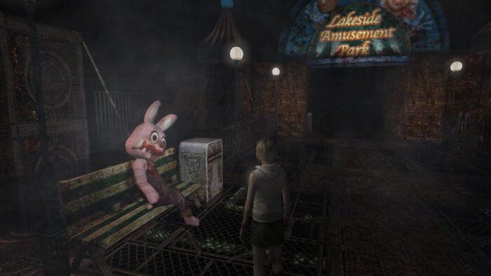 Heather stands in a twisted version of Lakeside Amusement Park. A bloody Robbie the Rabbit sits on a bench in front of her.