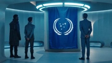 Book (David Ajala), Burnham (Sonequa Martin-Green) and Suhil (Adil Hussain) stand in a white room illuminated with white lights facing the blue flag with two white laurels in the center surronding 6 white stars