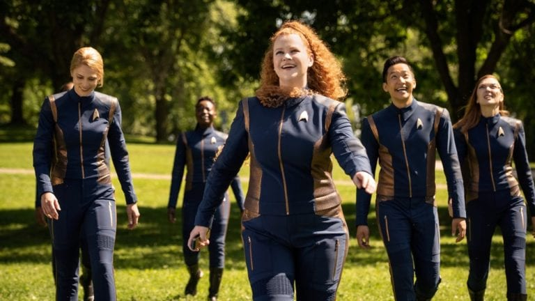 The Discovery bridge crew, with Tilly in the center, stand in the sun on a tree lined part of the old StarFleet academy campus and run toward the great tree
