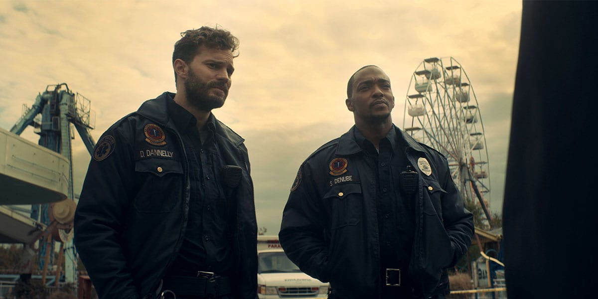 Jamie Dornan and Anthony Mackie in Synchronic. They're at an amusement park