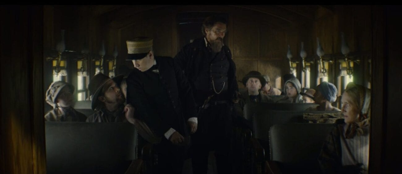 a crowded train interior with John Brown (Ethan Hawke) standing in the center with his gun visible at his hip, a passenger is whispering to the conductor who is standing to the left, while Onion and other passengers look on from the right